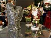 Above, top, a Santa Claus figurine made from a mid-19th-century German chocolate mold; and bottom, Sherrie Morin of South Grafton looks over some ornaments.