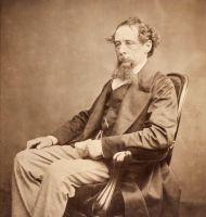 Albumen photograph of Charles Dickens, circa 1860s, seated in an armchair and looking to his left.