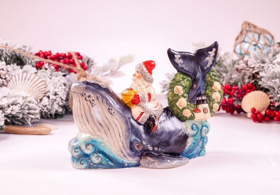A traditional Vaillancourt Santa in red riding a blue whale with a wreath with shells and Brant Point Lighthouse on his tail.